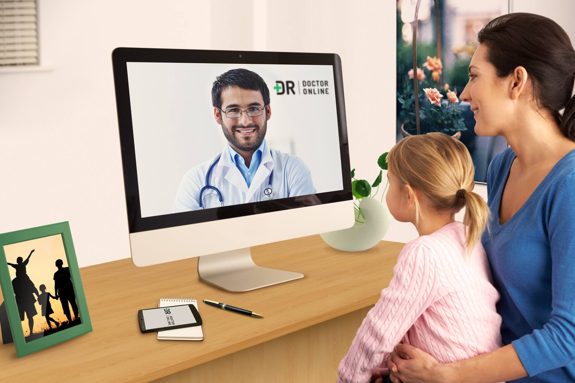 woman and girl looking at screen of doctor